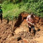 The Water Project: Jivovoli Community -  Clearing Spring Area For Protection