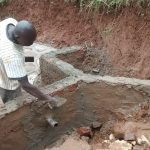 The Water Project: Jivovoli Community A -  Constructing Spring Wall