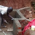 The Water Project: Jivovoli Community, Gideon Asonga Spring -  Inserting Pipe Into Spring