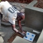 The Water Project: Jivovoli Community, Gideon Asonga Spring -  Laying Tile