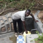 The Water Project: Masera Community -  Collecting Water From Protected Spring
