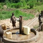 The Water Project: Nyakarongo Community -  Using The Rehabilitated Well