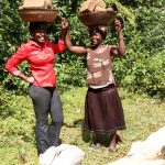 The Water Project: Ejinja Community, Anekha Spring -  Women Carrying Materials To The Artisan