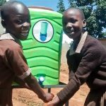 The Water Project: Mwanzo Primary School -  Anjala And Belinda Washing Their Hands After Visiting The Latrine