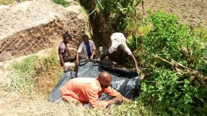 The Water Project:  Covering The Source Area With Plastic