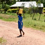 The Water Project: Ikoli Primary School -  Student Carrying Water
