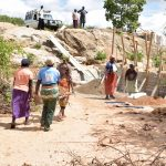 The Water Project: Ilandi Community -  Transporting A Heavy Stone To The Dam