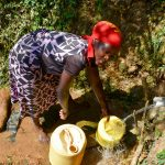 The Water Project: Mungakha Community, Nyanje Spring -  Jackline Fetching Water
