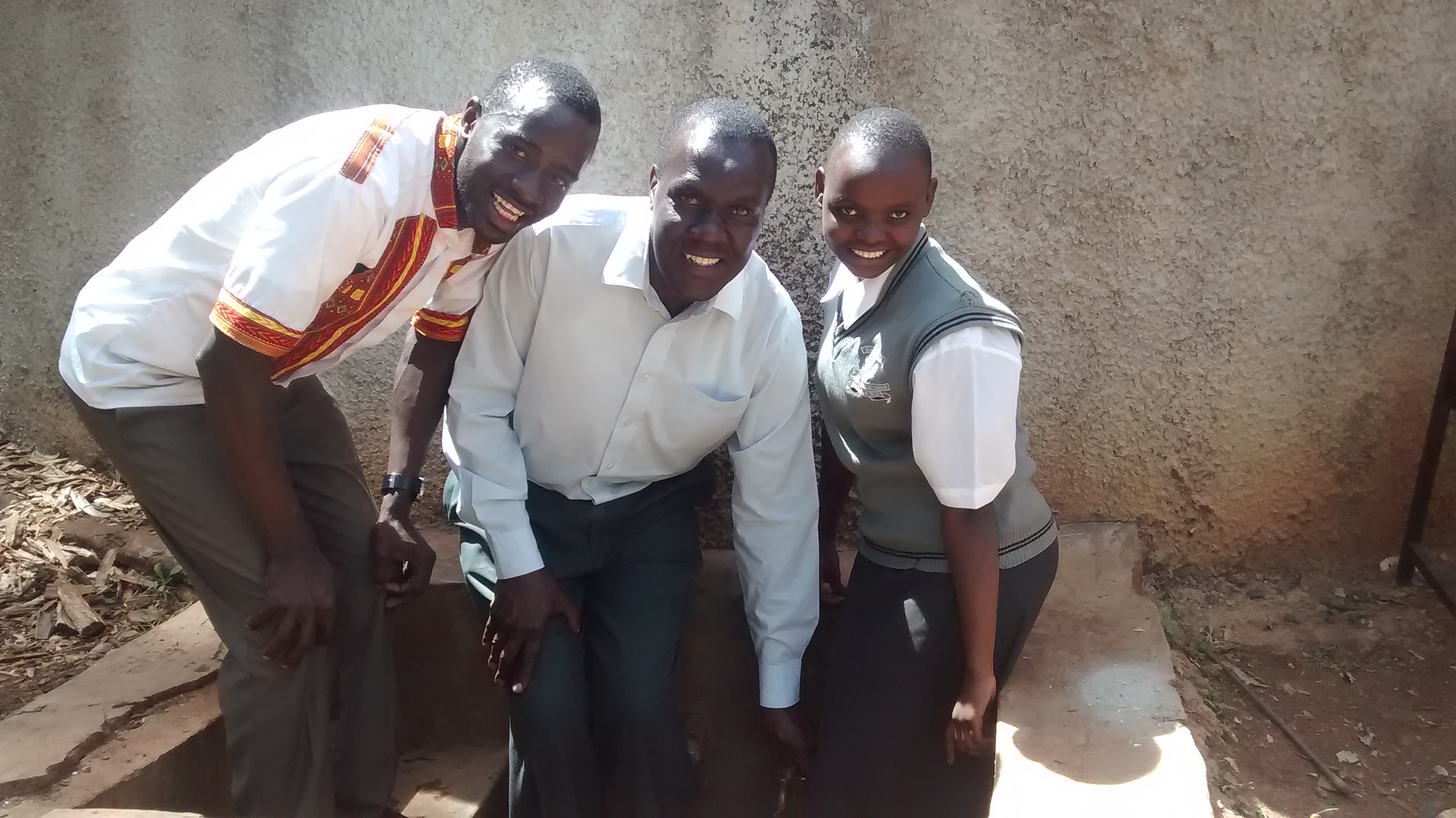 The Water Project : kenya4640-eric-wagaka-poses-with-teacher-and-student-at-the-tank