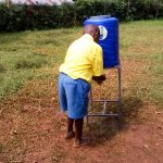 The Water Project: Eshilibo Primary School -  Student Using New Handwashing Station