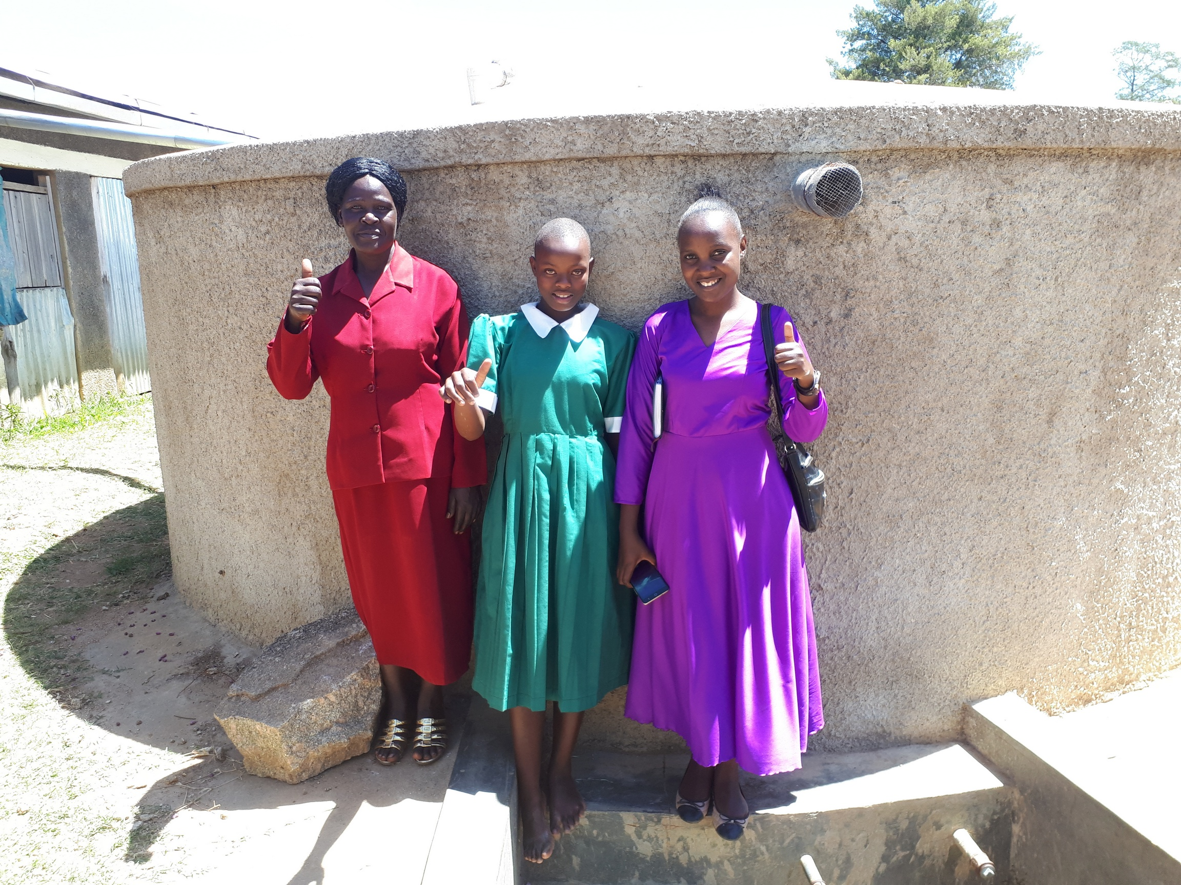 The Water Project : kenya4657-field-staff-joan-were-with-alice-and-jackyline-at-the-tank