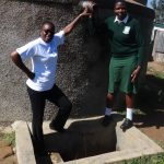 The Water Project: Ibinzo Girls Secondary School -  Field Officer Mary Afandi And Maureen Lumula At The Tank