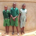 The Water Project: Emukangu Primary School, Butere -  Deograciuos Ouma And Fellow Students Pose In Front Of Tank