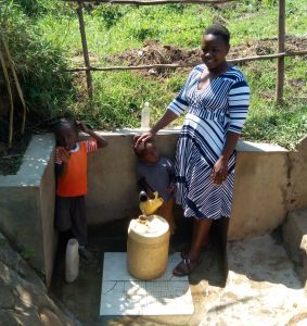 The Water Project:  Celinia Makomere And Her Family Stand At The Spring