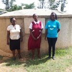 The Water Project: Bukura Primary School -  Field Staff Bomji In Blue Poses For A Picture At The Tank With Mrs Andayi And Laura