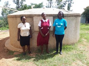 The Water Project:  Field Staff Bomji In Blue Poses For A Picture At The Tank With Mrs Andayi And Laura