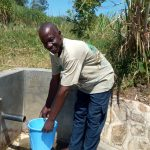 The Water Project: Chegulo Community, Shakava Spring -  Tom Shakava Collecting Water