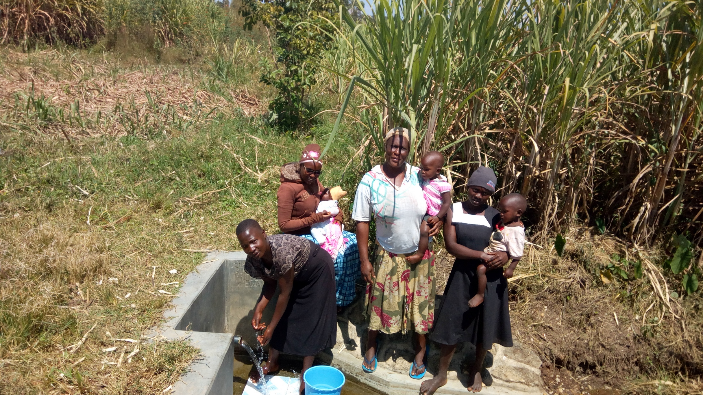 The Water Project : kenya4846-women-from-the-community-lined-up-to-fetch-water-from-the-spring