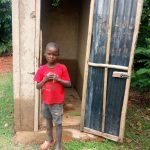 The Water Project: Timbito Community A -  A Boy Poses In Front Of A Latrine Constructed By A Sanplat