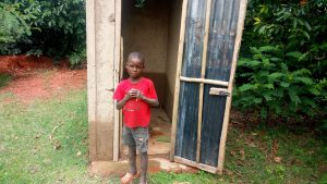 The Water Project:  A Boy Poses In Front Of A Latrine Constructed By A Sanplat