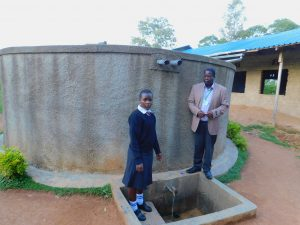 The Water Project:  Elizabeth Koome And Principal Rocken Ilahalwa Pose At The Tank