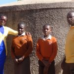 The Water Project: Compassion Primary School -  Field Staff Poses With Medina Achieng And Mark Okinyi At The Water Tank