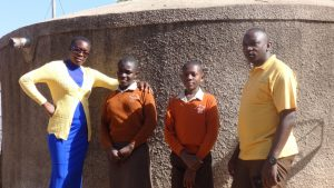 The Water Project:  Field Staff Poses With Medina Achieng And Mark Okinyi At The Water Tank