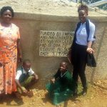 The Water Project: Esibuye Primary School -  Esther Asitiba And Agnes Mbooni Pose At The Tank With Field Officer Lillian Achieng