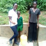 The Water Project: Handidi Community, Matunda Spring -  Field Officer Olivia Bomji Poses With Samson Matunda And His Mother At The Spring