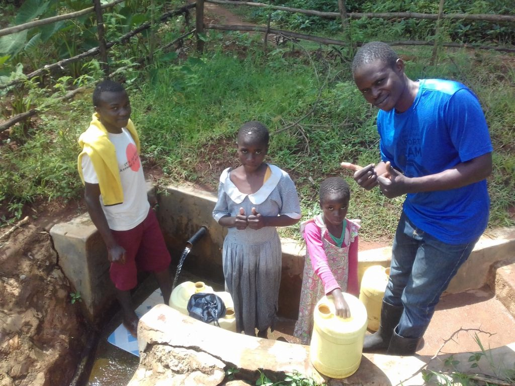 The Water Project : kenya4851-lai-baraka-her-daughters-and-field-officer-samuel-simidi-at-the-spring