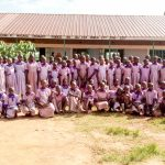 The Water Project: Magaka Primary School -  Students And Staff Posing In Front Of Classrooms