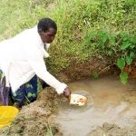 The Water Project: Musango Community, Ndalusia Spring -  Eldah Getting Water