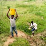 The Water Project: Musango Community, Ndalusia Spring -  John Helping Eldah Carry Water Back Home