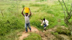 The Water Project:  John Helping Eldah Carry Water Back Home