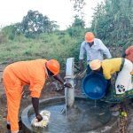 The Water Project: Nyakarongo Center Community -  Rinsing Down The Area After Pump Installation
