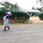 The Water Project: Magaka Primary School -  School Cook Carrying A Meal Across The Road