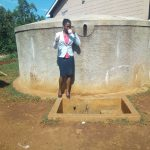 The Water Project: El'longo Secondary School -  Margaret Egesa Drinks Water From The Tank