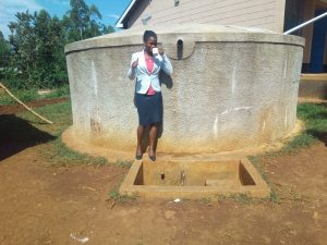 The Water Project:  Margaret Egesa Drinks Water From The Tank