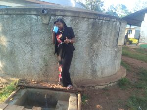The Water Project:  Field Officer Jacklyne Chelagat Drinks From The Tank
