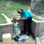 The Water Project: Futsi Fuvili Community, Shikanga Spring -  A Young Girl And Field Officer Joan Were At The Spring