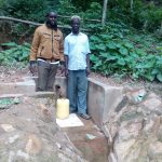 The Water Project: Elunyu Community, Saina Spring -  Field Officer Wilson Kipchoge And Herman Kaongeli