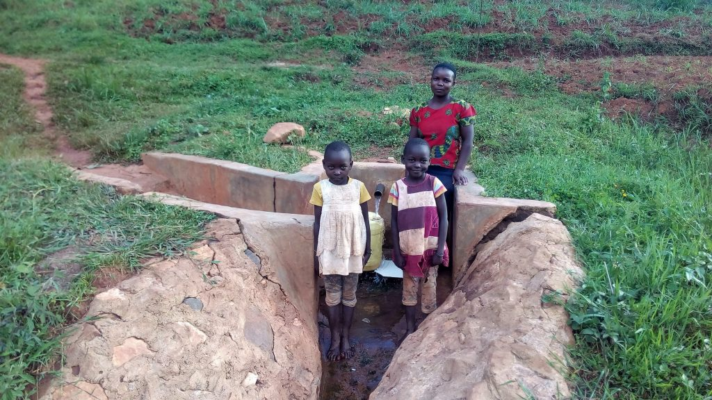 The Water Project : kenya4752-posing-in-front-of-the-spring-a-year-after-it-was-protected