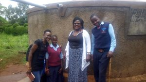 The Water Project:  Field Officer Lillian Achieng And Esther Minayo With Headteacher Veronica Onacha