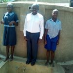 The Water Project: Namalenge Primary School -  Headteacher Alex Ywaya Posing With Lvenda Adeya And Owen Wanaami At The Tank