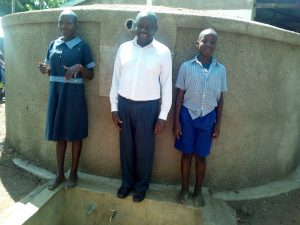 The Water Project:  Headteacher Alex Ywaya Posing With Lvenda Adeya And Owen Wanaami At The Tank