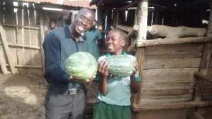 The Water Project:  Field Officer Erick Wagaka And Dan Carrying Pumkin Fruit Harvested From The School Farm
