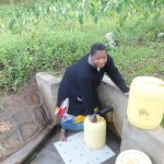 The Water Project: Shitungu Community, Mmbone Spring -  Josephine Mmbone Fetches Water From The Spring