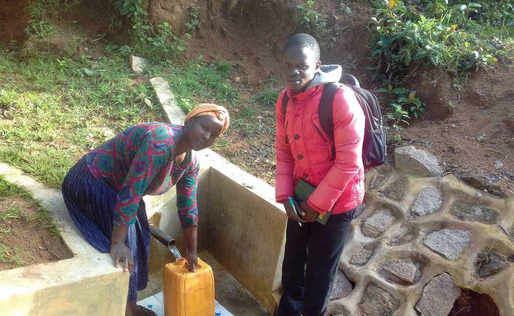 The Water Project : kenya4854-field-officer-samuel-simidi-with-lydia-sayo-at-the-spring
