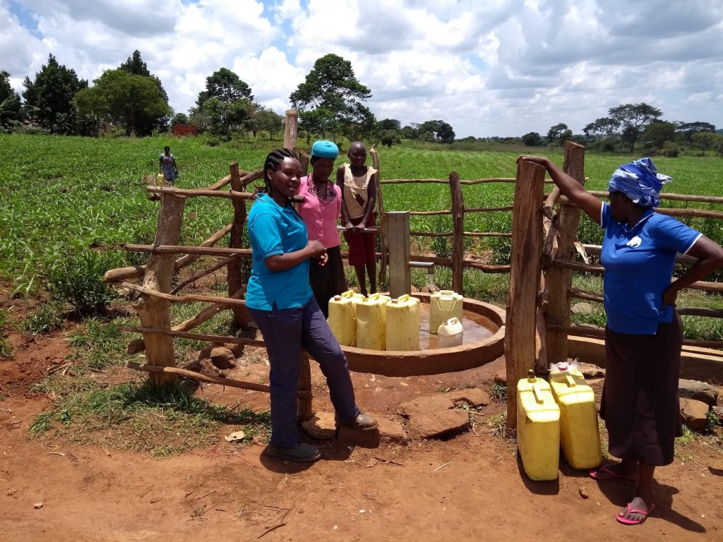 The Water Project : uganda6081-field-officer-olive-chatting-with-the-community-members