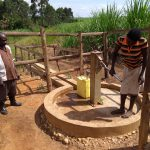 The Water Project: Rubona Kyagaitani Community -  Community Members Using The Water Point